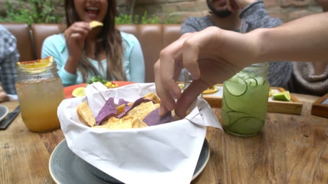 Group of friends eating Nachos at a restaurant