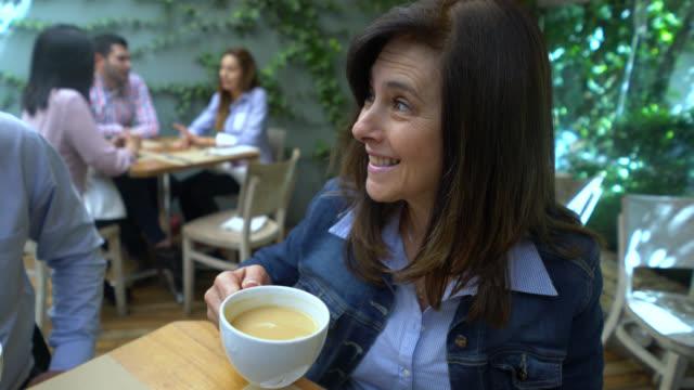 Groep vrienden genieten van een kopje koffie en te praten op zoek gelukkig en lachende