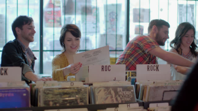 Group of friends flip through stacks of vintage vinyl in Austin record store