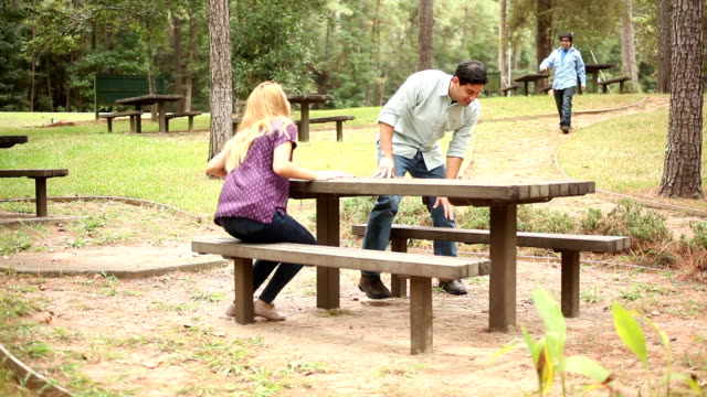 Group of friends gathering at picnic table in park.