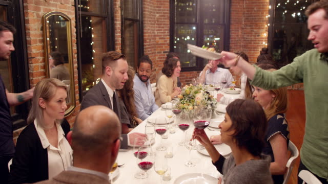 MS Group of friends having entrees served to them during dinner party in loft