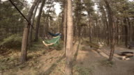 Group of friends laying in hammocks under trees
