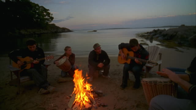 MS, Group of friends  playing guitars around beach campfire, Cow Island, Maine, USA