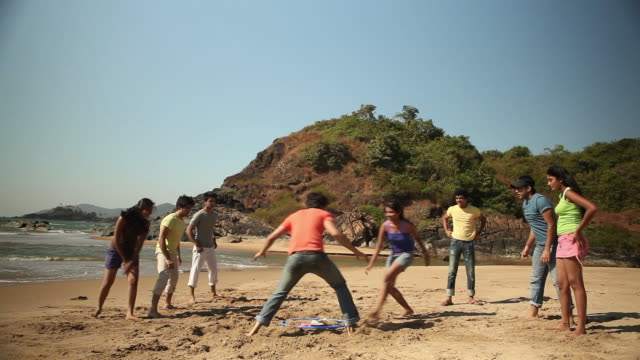 Group of friends playing on the beach