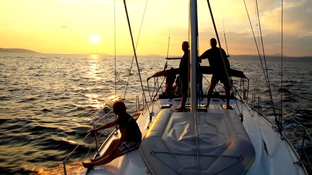 Gruppo di amici in barca a vela al tramonto