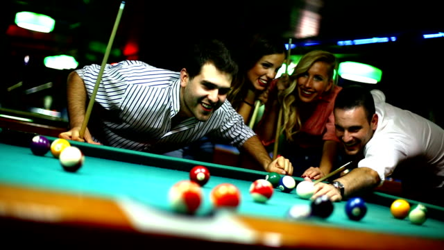 Group of friends shooting pool on a night out.
