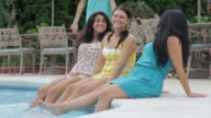 MS Group of friends sitting around swimming pool outdoors / East Hanover, New Jersey, United States