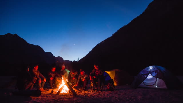 Groep vrienden zitten bij het kampvuur, verhalen uit te wisselen
