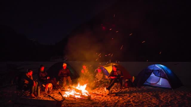 Groep vrienden zitten bij het kampvuur