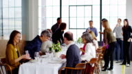 MS group of friends sitting down at banquet table at dinner party in loft