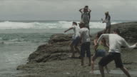 A group of friends skimming stones by the shore.