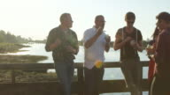 MS Group of friends standing on dock during party at sunset eating dessert