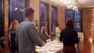 MS Group of friends taking seats at table during dinner party in loft
