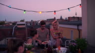 A group of friends talk on an urban rooftop