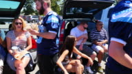 MS PAN Group of friends talking and barbecuing during tailgating party before football game