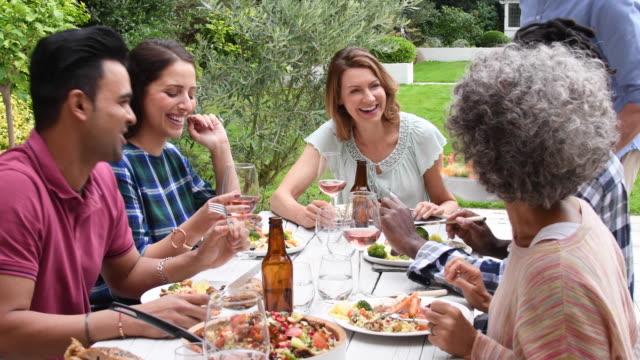 Groep vrienden praten en ontspannen samen tijdens de lunch buiten