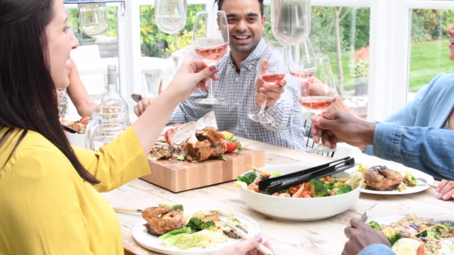 Group of friends toasting and drinking rose wine over dinner