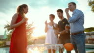 Group of friends tossing wine in social gathering