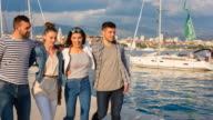 MS group of friends walking arm in arm through yacht harbor