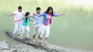 Group of friends walking on a fallen tree at riverbank