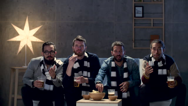 Group of friends watching sport on tv.