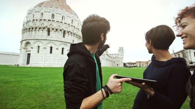 Gruppe von Freunden mit digitalen Führer der Piazza dei Miracoli