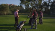 DS group of golfers (mature and young couple) on fairway, camera moves around clockwise (steadycam) from rear to front, mature woman takes shot RED R3D 4K