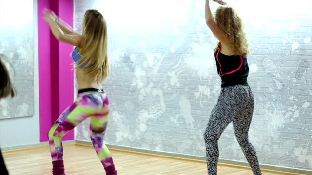 Group of happy women doing 'Zumba' dance fitness in class