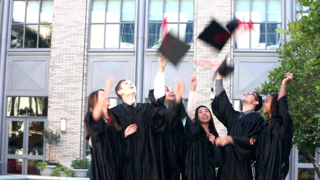 Group of high school graduates throwing caps in air
