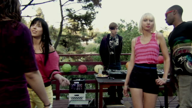 MS Group of hip young men and women dancing at party on outdoor deck with DJ/ Woman and DJ begin dancing in exaggerated manner with thumbs inserted through belt loops/ Los Angeles, California