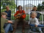 1972 group of hippies with baby in stroller sitting at White House gate / man playing guitar