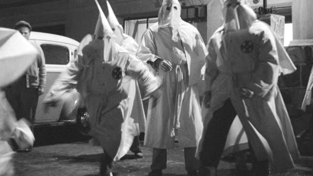 MS Group of hooded clansmen fire to gun than run toward