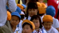 Group of Japanese school children walking with teacher Available in HD.