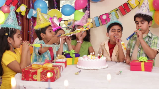 Group of kids blowing party blow horn in birthday celebration