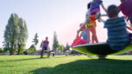 MS Group of kids playing on merry go round on playground
