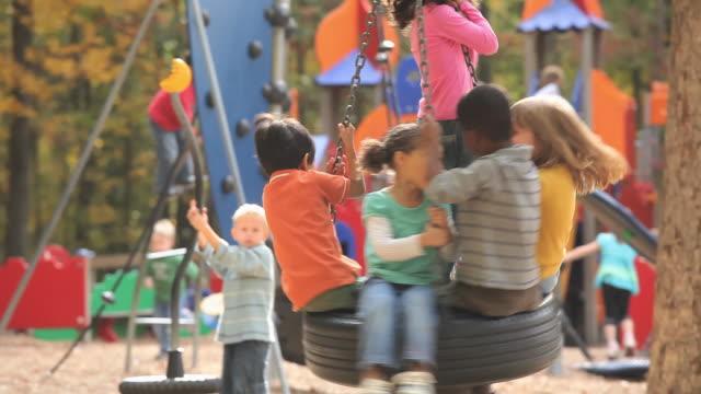 MS TU TD Group of kids (2-7) playing on playground tire swing / Richmond, Virginia, USA.