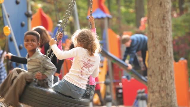 MS Group of kids (4-7) playing on playground tire swing / Richmond, Virginia, USA.