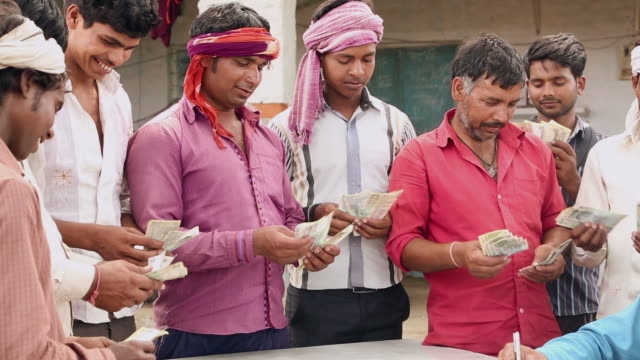 Group of labours counting indian rupees, Haryana, India