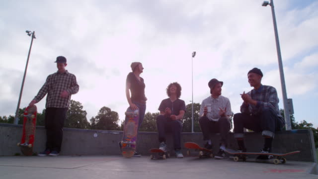 MS SLO MO Group of laughing male and female skateboarders hanging out in neighborhood skate park