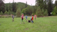 MS SLO MO TS Group of laughing young kids having water balloon fight on grass field at summer camp