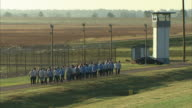 Group of male criminal prisoners walking in group on asphalt road outside maximum security prison fencing toward guard tower Incarceration not jail...