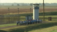 Group of male criminal prisoners walking on asphalt road outside maximum security prison fencing by guard tower followed by prison bus guard walking...