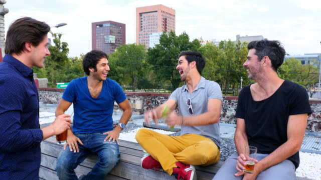 MS SWISH PAN Group of male friends laughing and sharing drinks on rooftop deck