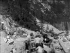 B/W 1929 group of men carrying boxes of dynamite on mountainside / newsreel