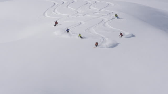 A group of men helicopter skiing on a snow covered mountain. - Slow Motion - filmed at 240 fps