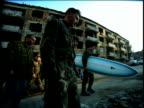 Group of men in military fatigues (one carrying surfboard) walking / ruins of bldgs in background / Sarajevo