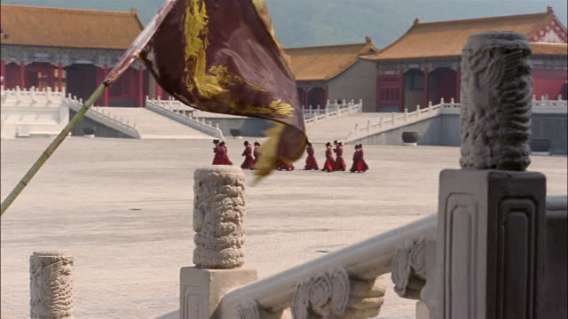 A group of men in red robes walk through the courtyard of the Forbidden City.