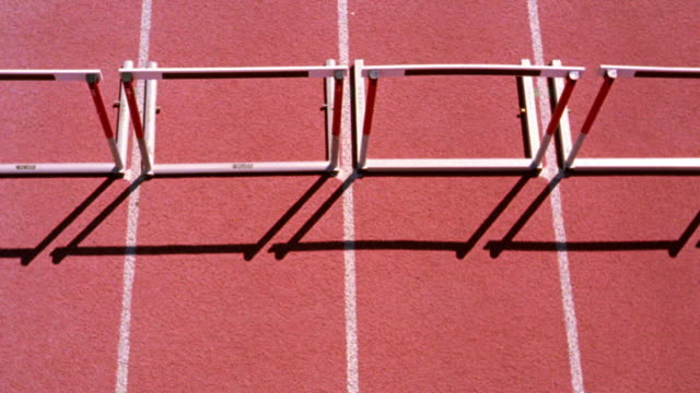 OVERHEAD group of men jumping hurdles in race on track