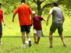 SLO MO,  SHAKY,  SWISH PAN,  group of men kicking ball in park,  Miami,  Florida,  USA