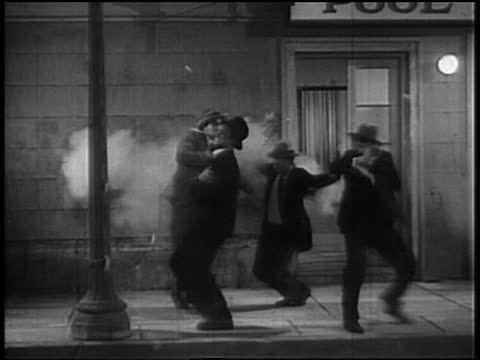 B/W 1932 group of men on sidewalk being shot by passing car followed by second car shooting at first